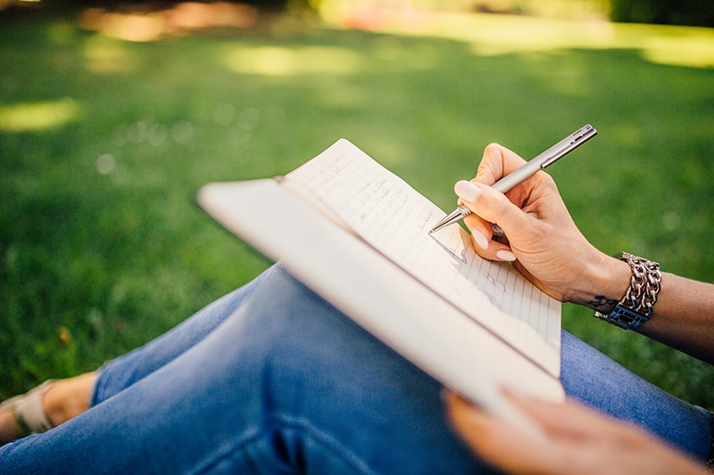 Female entrepreneur writing in a notebook in a green field